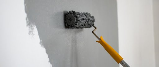 Man painting interior of home
